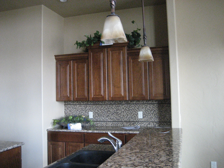 Kitchen cabinets at staggered heights with mosaic tile treatment below