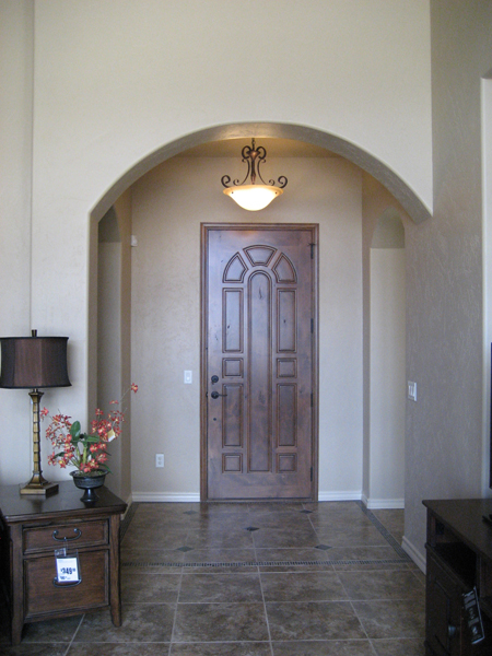 Entry with custom carved wood door and arch into great room