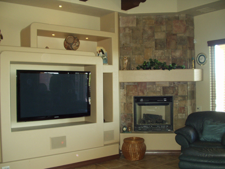 Custom designed entertainment center with floating tv and cornerfireplace with stone face