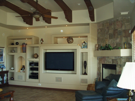 This custom designed entertainment center has lighted nichos and floating tv