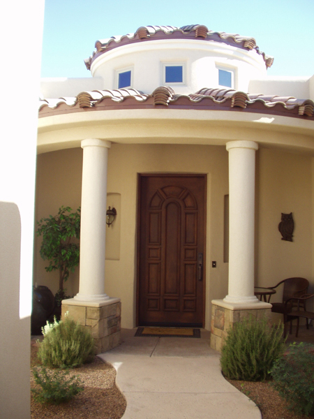 Covered front porch has columns with stone bases, tile roof and celerstories